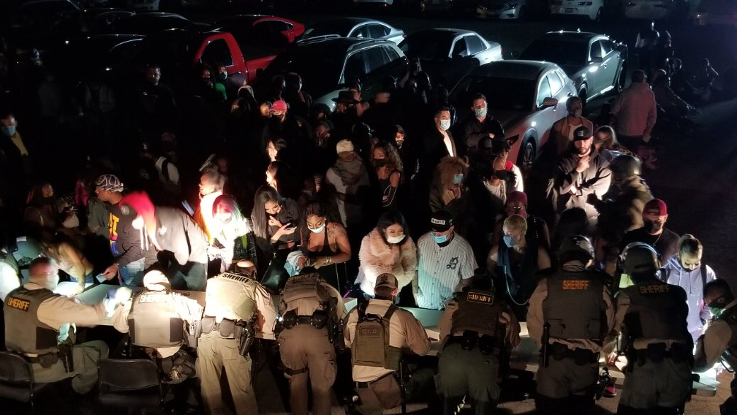People line up to be cited after deputies busted an underground party being held in Los Angeles in violation of public health orders during the COVID-19 pandemic on Jan. 14, 2020, in a photo released by the Los Angeles County Sheriff's Department.