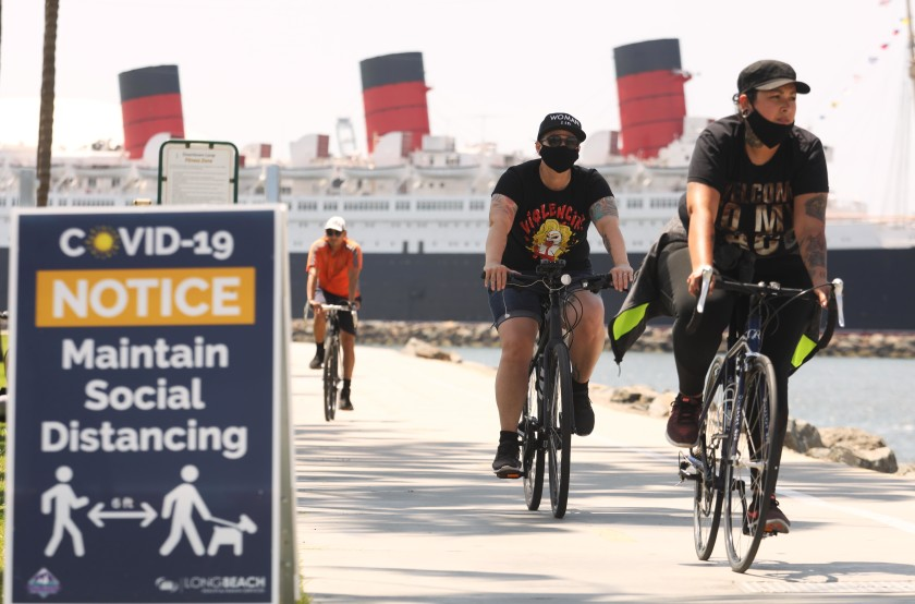 With the Queen Mary in the background, cyclists in Long Beach make their way along a bike path in May 2020. The company that operates the former ocean liner filed for bankruptcy protection. (Genaro Molina / Los Angeles Times)