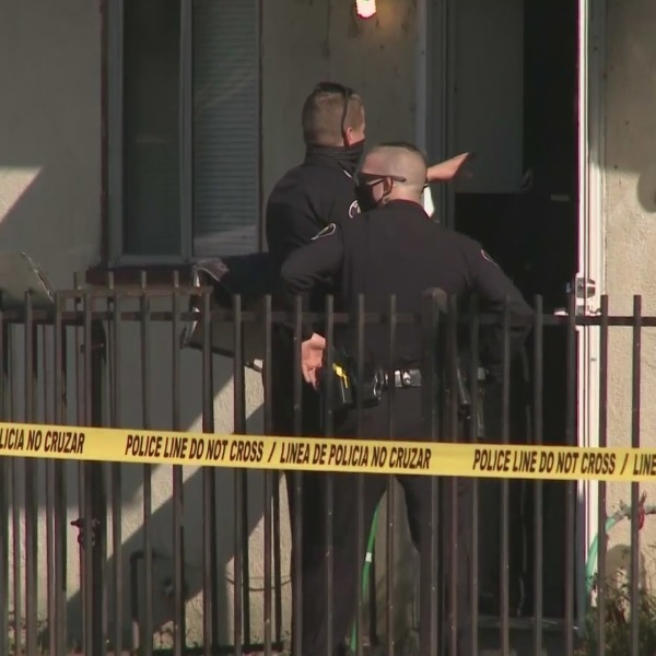 Detectives investigate after a man was found dead and a woman injured in Santa Ana on Jan. 21, 2021. (KTLA)