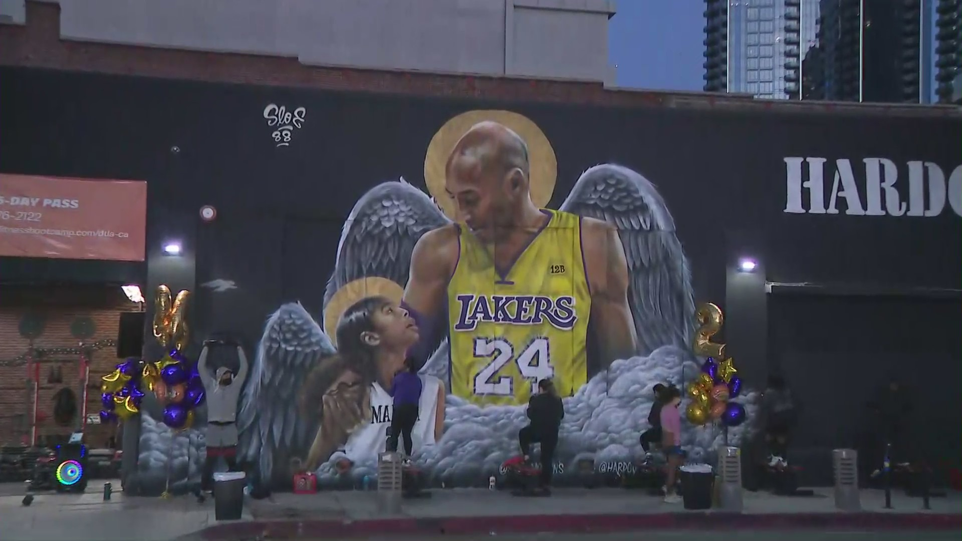 People gather at a Kobe and Gianna Bryant mural at Pico Boulevard and Grand Avenue in downtown Los Angeles on Jan. 26, 2021, a year after their death.