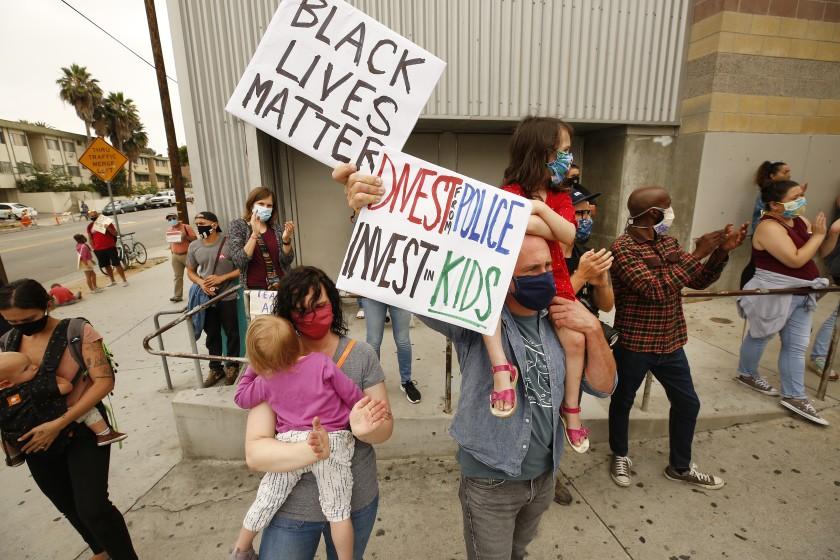 托尼-卡斯特罗和他的妻子德文-哈洛(Devon Harlow)在2020年6月学生活动家和社区成员的抗议活动中,抱着他们5岁的女儿Adife和2岁的Niamh,敦促洛杉矶联合学区资助学校警察并取消其预算。(Al Seib / Los Angeles Times)(photo:KTLA)