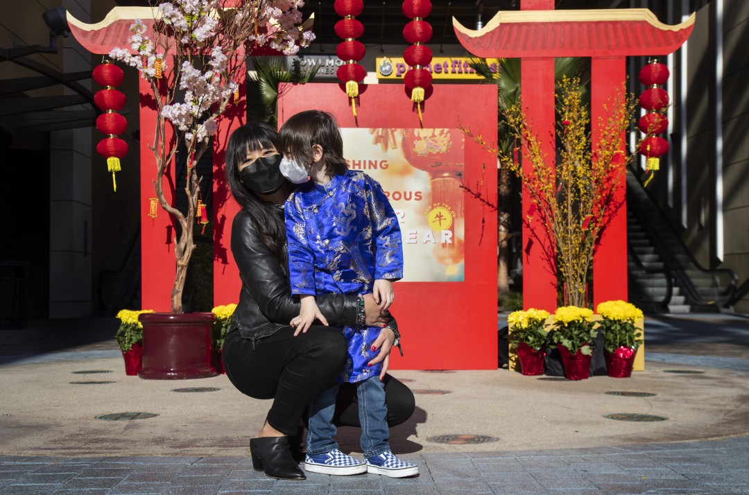 Kat Nguyen-De Angelis is seen with her son Dominic, 4, at the pagoda photo display under a sea of red lanterns at the Union Market in Tustin in an undated photo.(Gina Ferazzi / Los Angeles Times)
