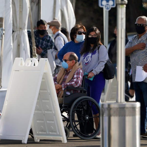 Orange County residents wait in line outside tents for a COVID-19 vaccine at the Toy Story parking lot at the Disneyland Resort Wednesday, Jan. 13, 2021, in Anaheim. (AP Photo/Damian Dovarganes)