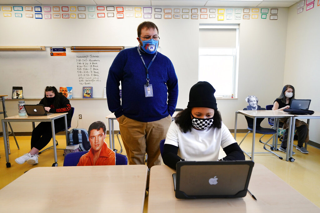 Social studies teacher Logan Landry looks over the shoulder of seventh grader Simone Moore as she works on a project while seated next to a cutout of Elvis Presley at the Bruce M. Whittier Middle School, Jan. 29, 2021, in Maine.(AP Photo/Robert F. Bukaty)