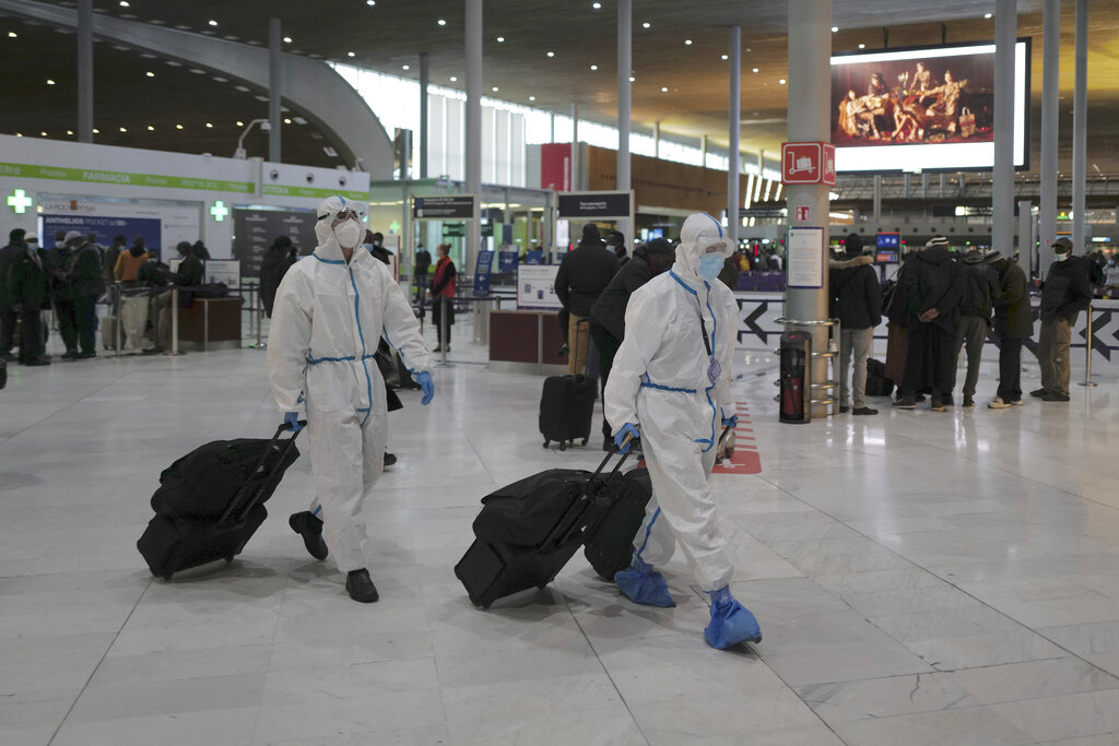 Passengers from Taiwan wearing protective gear arrive to board their plane at Paris Charles de Gaulle Airport in Roissy , north of Paris, Monday, Feb. 1, 2021. (AP Photo/Francois Mori)