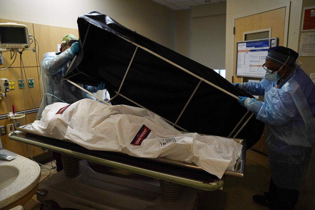 In this Jan. 9, 2021, file photo, transporters prepare to move a body of a COVID-19 victim to a morgue at Providence Holy Cross Medical Center in Mission Hills. (AP Photo/Jae C. Hong, File)