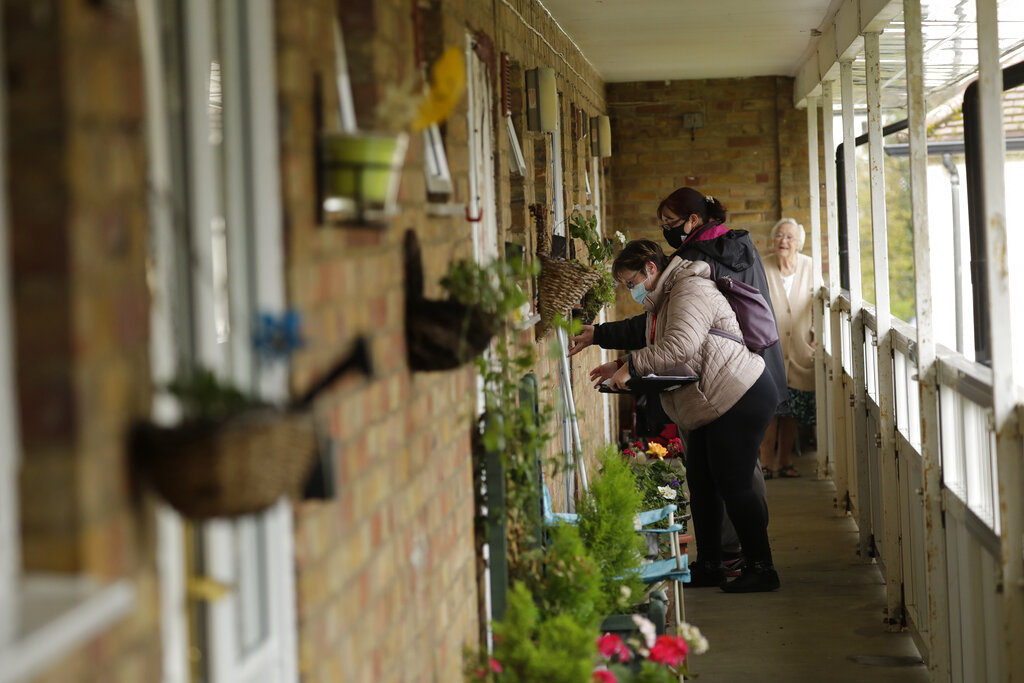 Distributors working in a pair together go door-to-door giving out home testing kits for COVID-19 from Britain's Department of Health, in Woking, England, Tuesday, Feb. 2, 2021, during England's third national lockdown since the coronavirus outbreak began. (AP Photo/Matt Dunham)