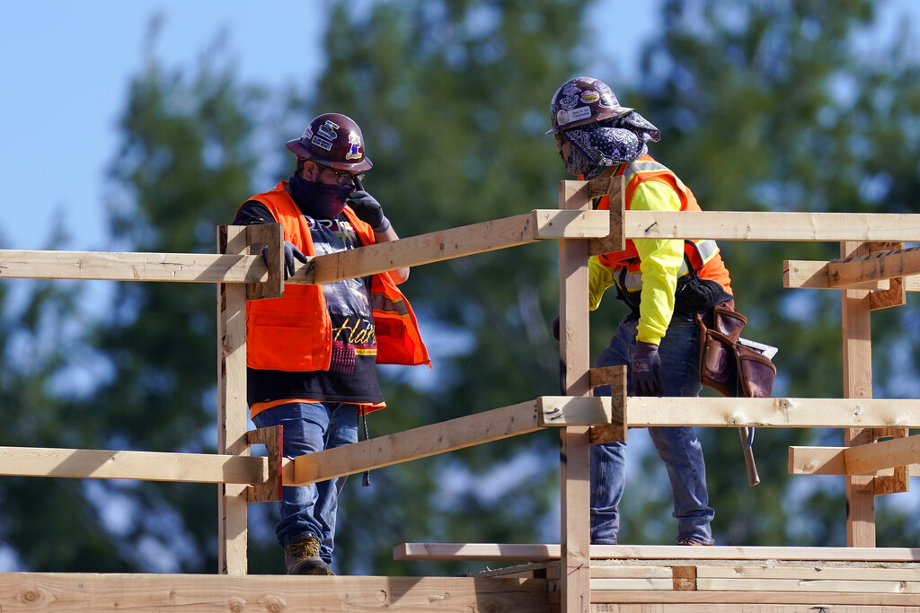 Construction workers talk at a USA Properties Fund site on Feb. 2, 2021, in Simi Valley, Calif. (AP Photo/Mark J. Terrill)