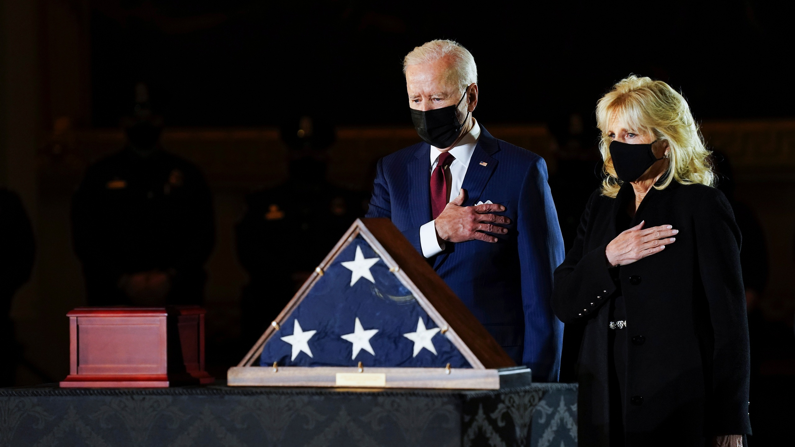 President Joe Biden and first lady Jill Biden pay their respects to the late U.S. Capitol Police Officer Brian Sicknick as an urn with his cremated remains lies in honor on a black-draped table at center of Capitol Rotunda on Feb. 2, 2021. (Erin Schaff / The New York Times via Associated Press)