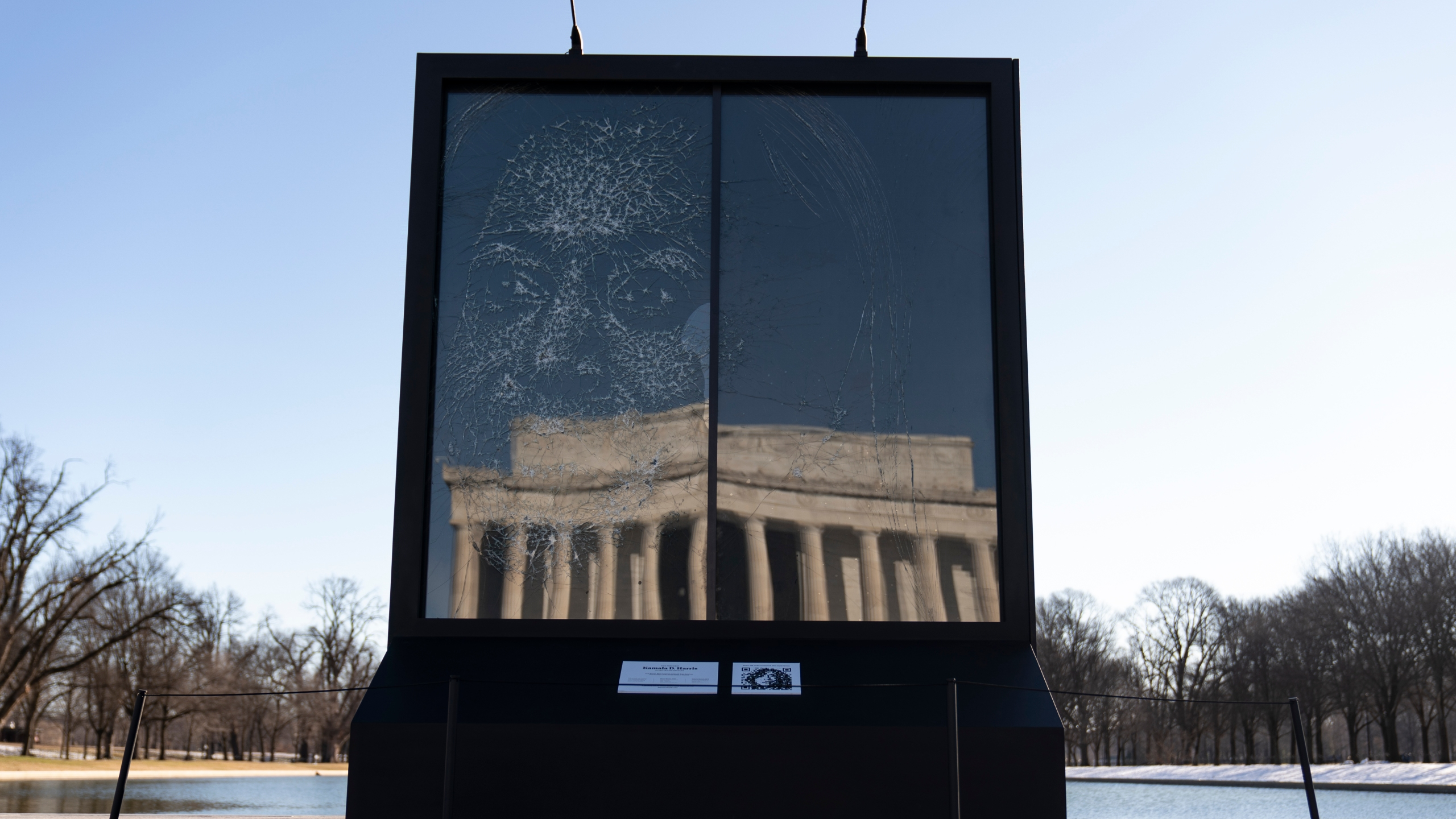 """The installation """"Vice President Kamala Harris Glass Ceiling Breaker"""" is seen at the Lincoln Memorial, reflected, in Washington, Wednesday, Feb. 4, 2021. Vice President Kamala Harris' barrier-breaking career has been memorialized in a portrait depicting her face emerging from the cracks in a massive sheet of glass. Using a photo of Harris that taken by photographer Celeste Sloman, artist Simon Berger lightly hammered on the slab of laminated glass to create the portrait of Harris. (AP Photo/Carolyn Kaster)"""