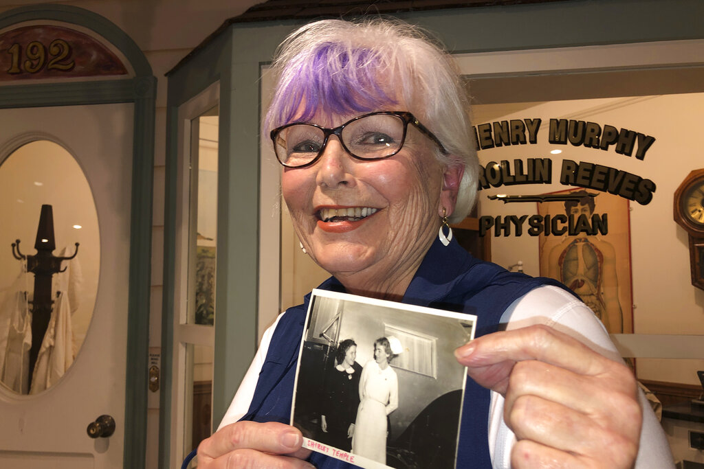 Nurse practitioner Sigrid Stokes, 76, holds a photograph of her mother talking to Shirley Temple, at the Salinas Valley Memorial Hospital in Salinas, Calif., Wednesday, Feb. 3, 2021. (AP Photo/Haven Daley)