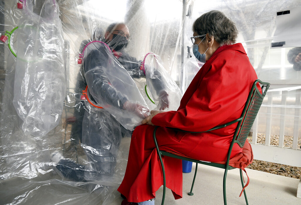 """Gregg MacDonald holds hands with his 84-year-old mother, Chloe MacDonald, at a """"hug tent"""" set up outside the Juniper Village assisted living center in Louisville, Colo., Wednesday, Feb. 3, 2021. (AP Photo/Thomas Peipert)"""