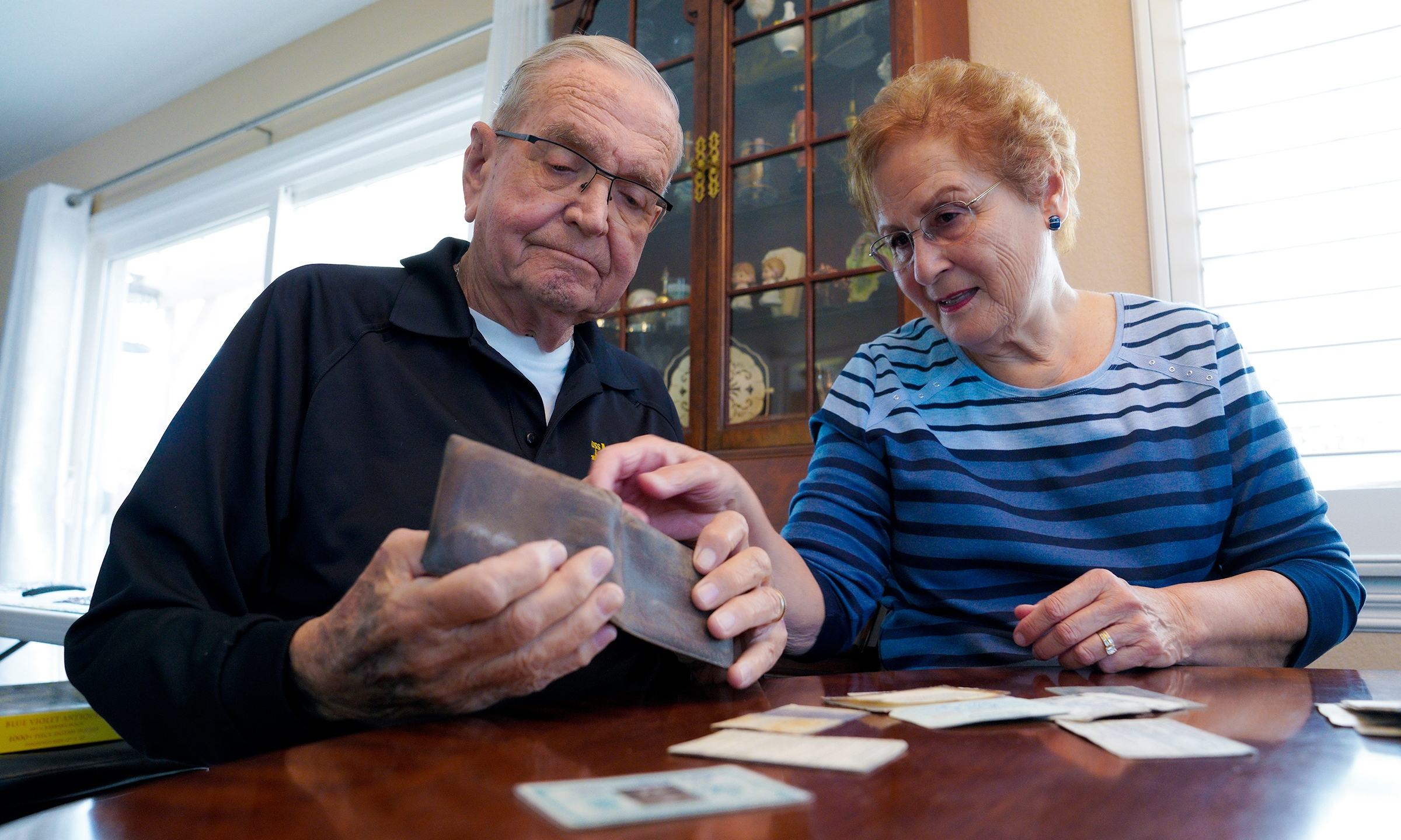 Paul Grisham and his wife Carole Salazar look over his wallet and the items that were inside when he lost the wallet back in 1968 at their home in the San Carlos section of San Diego, Calif., Wednesday, Feb. 3, 2021. Grisham's wallet was missing for so long he forgot all about it. Fifty-three years later, the 91-year-old has the billfold back along with mementos of his 13-month assignment as a Navy meteorologist on Antarctica in the 1960s. (Nelvin C. Cepeda/The San Diego Union-Tribune via AP)