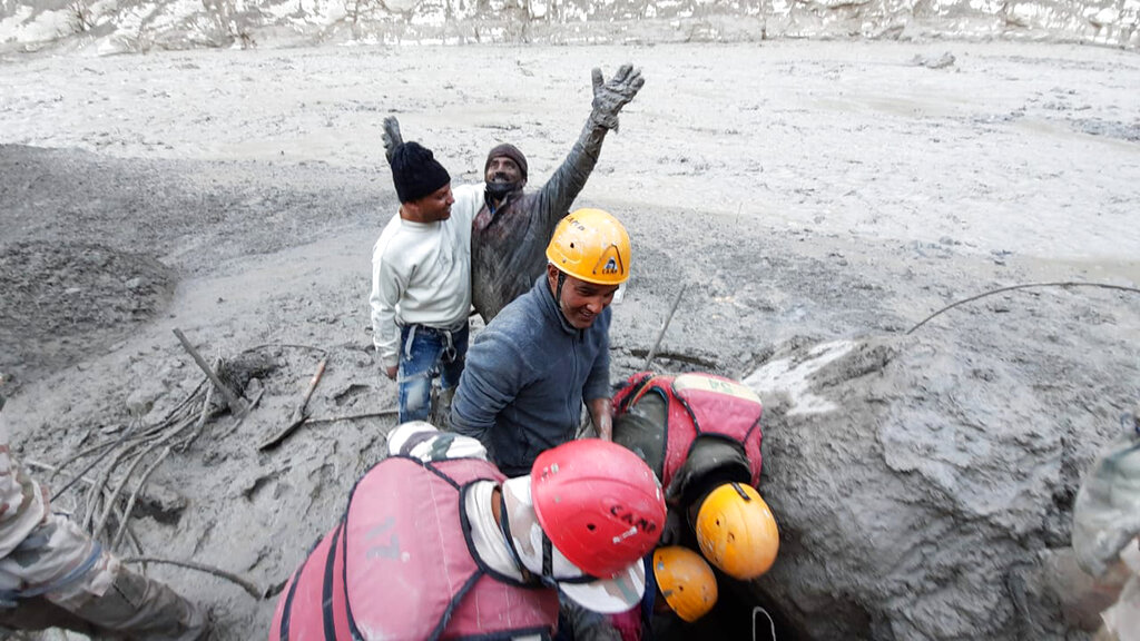 This photograph provided by Indo Tibetan Border Police (ITBP) shows a man reacting after he was pulled out from beneath the ground by ITBP personnel during rescue operations after a portion of Nanda Devi glacier broke off in Tapovan area of the northern state of Uttarakhand, India, Sunday, Feb.7, 2021. (Indo Tibetan Border Police via AP)