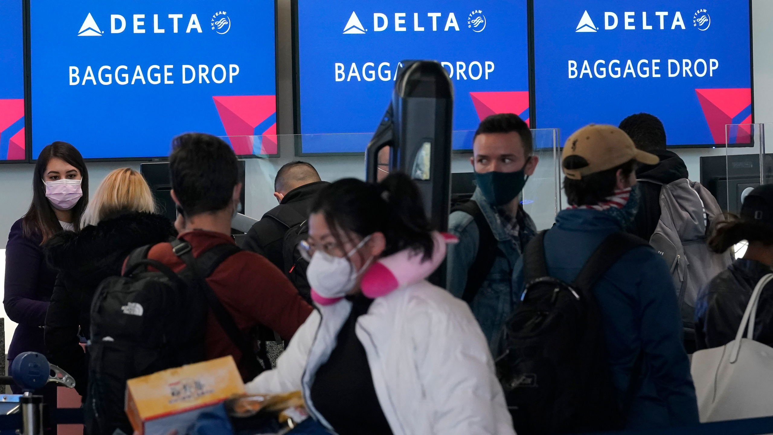 People wait in line at a Delta Air Lines gate at San Francisco International Airport during the coronavirus pandemic in San Francisco, Tuesday, Dec. 22, 2020. (AP Photo/Jeff Chiu)