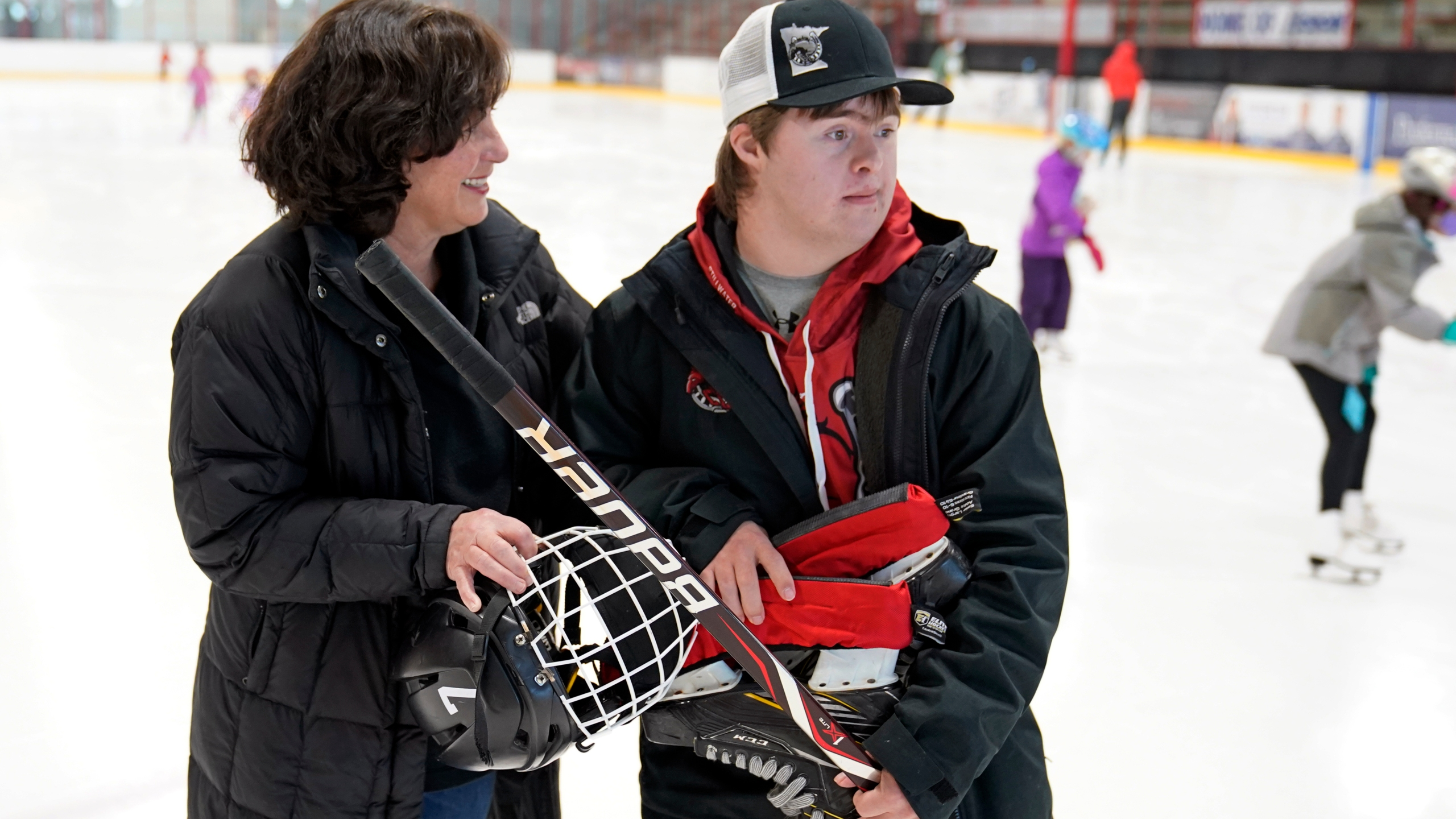 Suzy Lindeberg poses with her 20-year-old son John on a hockey rink, Tuesday, Feb. 9, 2021, in Stillwater, Minn. John, who has Down Syndrome, can't spend as much time at the rink as he used to since he is at higher risk for hospitalization or death if he caught COVID-19, but his mother and other advocates worry that the state of Minnesota has placed people with disabilities too far down the priority list. (AP Photo/Jim Mone)