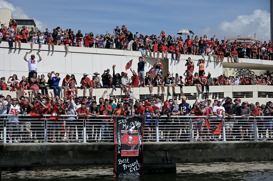 Fans watch the Tampa Bay Buccaneers celebrate their Super Bowl 55 victory over the Kansas City Chiefs with a boat parade in Tampa, on Feb. 10, 2021. (Phelan Ebenhack/Associated Press)