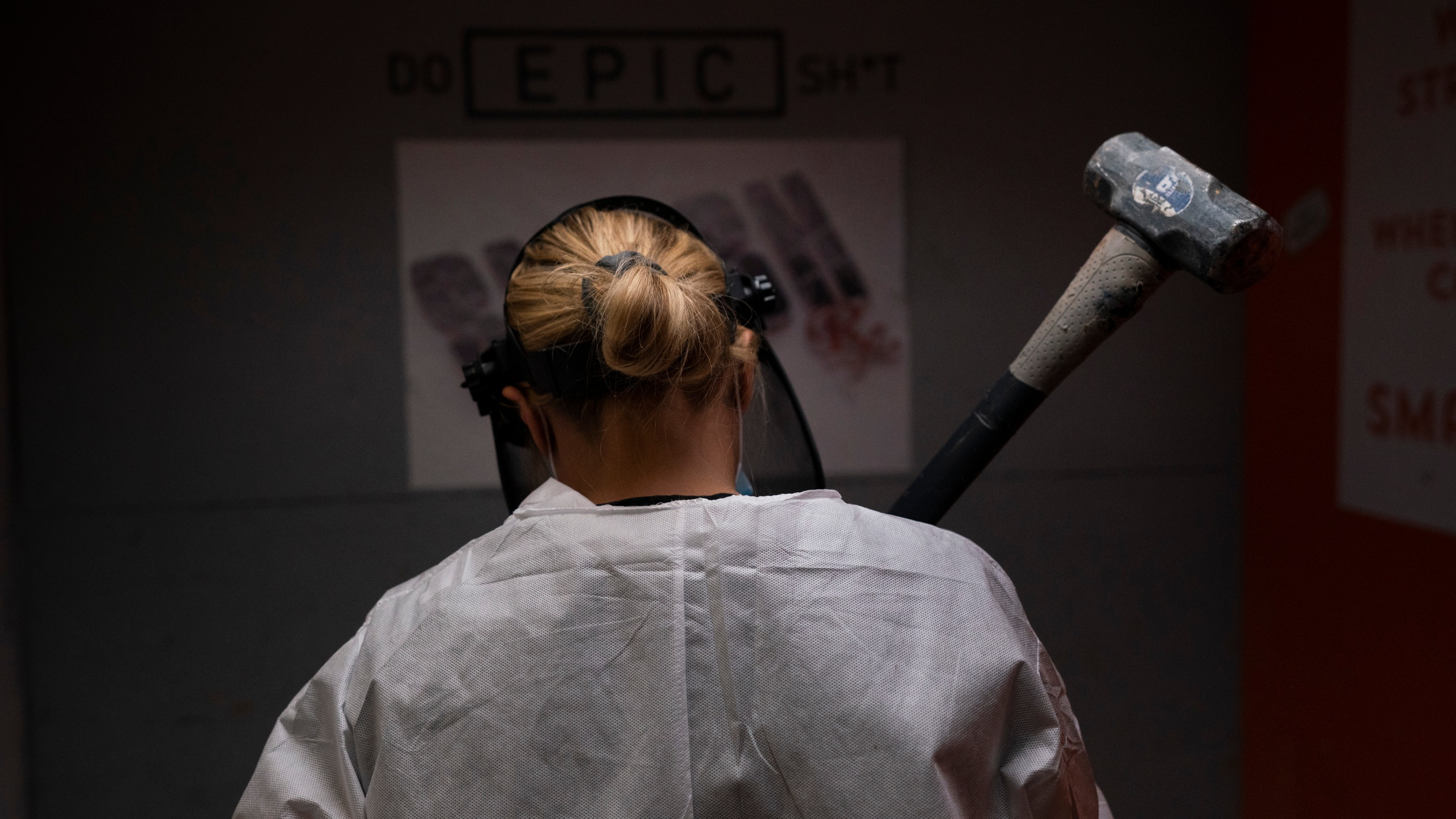 Michelle Elohim, a mother of four children, holds a hammer to smash a side table in a rage room at Smash RX in Westlake Village on Feb. 5, 2021. (Jae C. Hong / Associated Press)