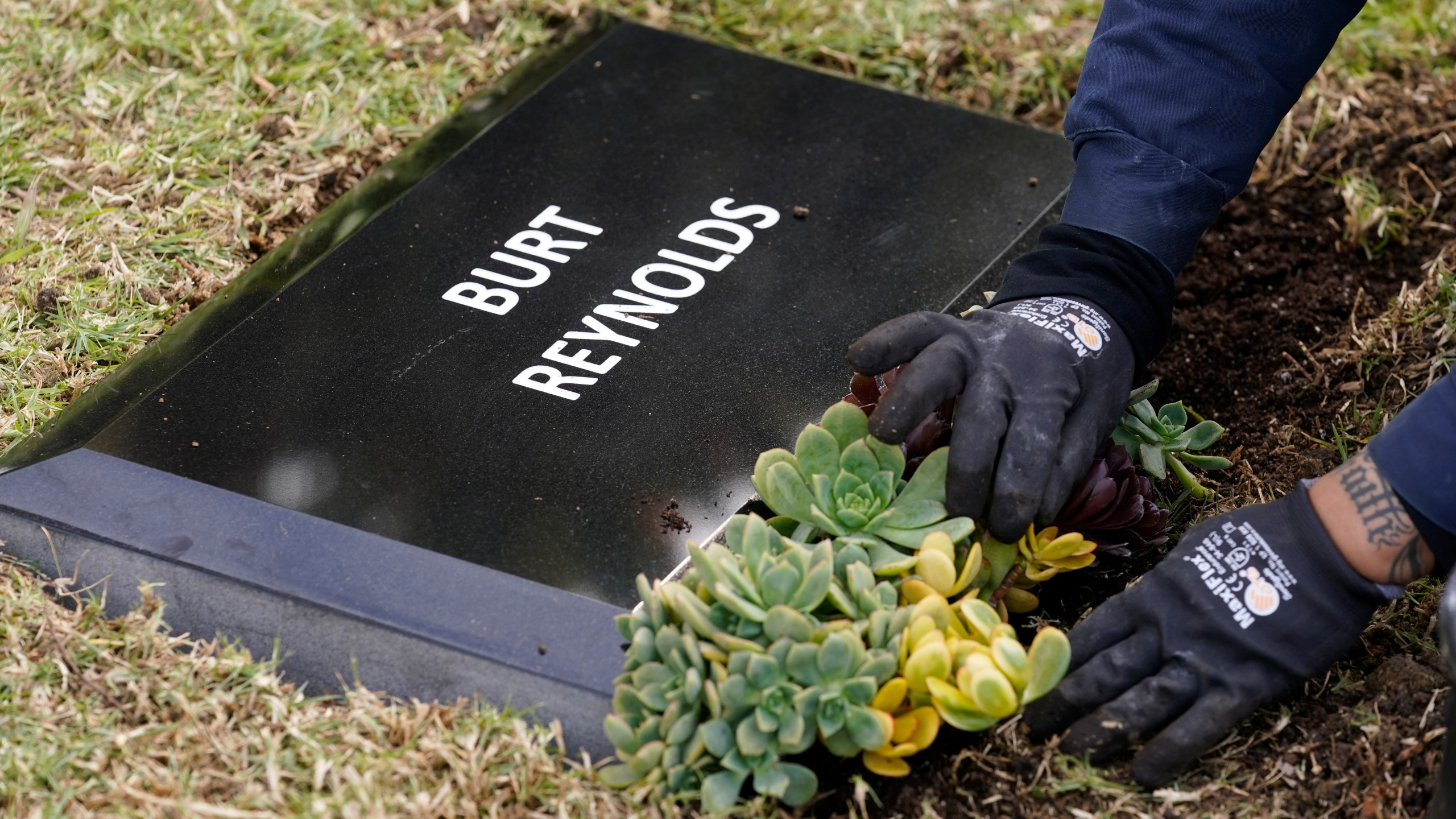 Flowers are placed in front of a temporary headstone for the late actor Burt Reynolds in the Garden of Legends section of Hollywood Forever cemetery, on Feb. 11, 2021. (Chris Pizzello/Associated Press)