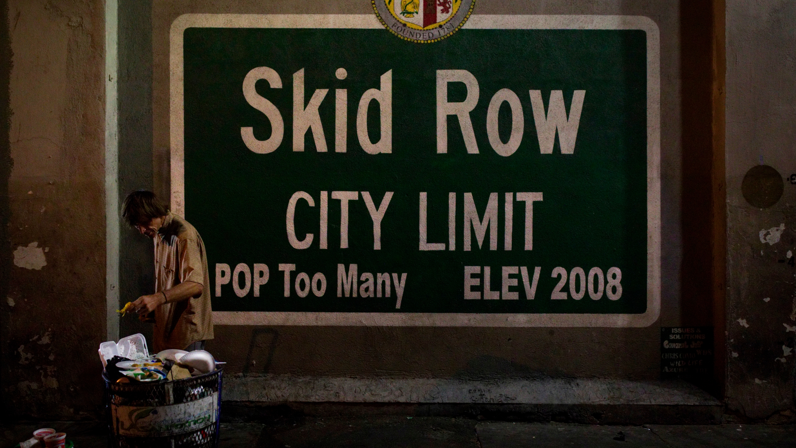 A homeless man takes food from a trash can in Los Angeles' Skid Row area, home to the nation's largest concentration of homeless people in Los Angeles, on Oct. 28, 2017. (Jae C. Hong / Associated Press)