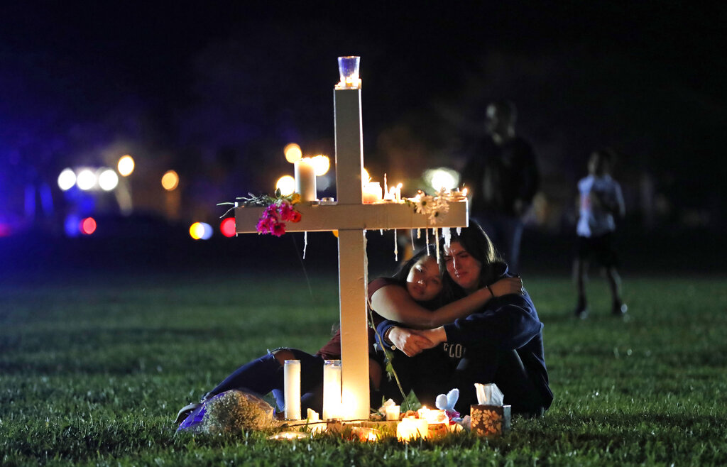 In this Feb. 15, 2018 file photo, people comfort each other as they sit and mourn at one of seventeen crosses, after a candlelight vigil for the victims of the shooting at Marjory Stoneman Douglas High School, in Parkland, Fla. (AP Photo/Gerald Herbert, File)