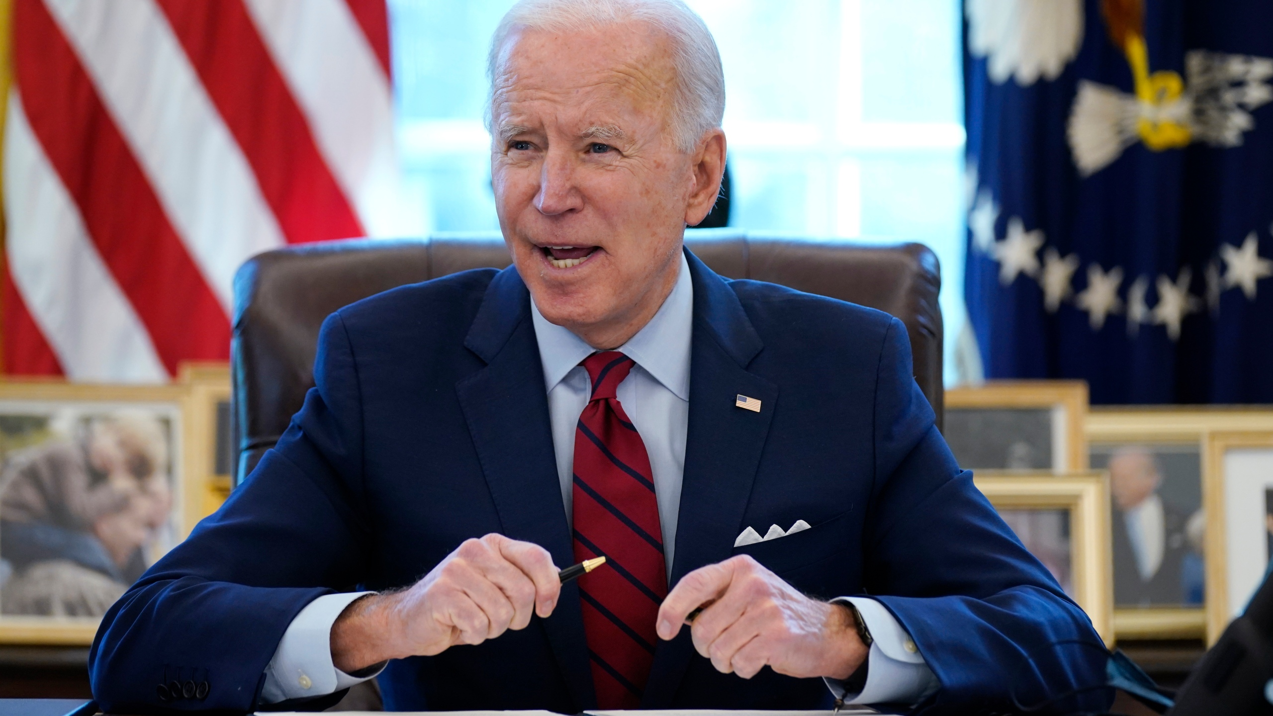In this Jan. 28, 2021 file photo, President Joe Biden signs a series of executive orders in the Oval Office of the White House in Washington. Biden campaigned on raising the national minimum wage to $15 per hour and attached a proposal doing just that to the $1.9 trillion coronavirus pandemic relief bill. (AP Photo/Evan Vucci)