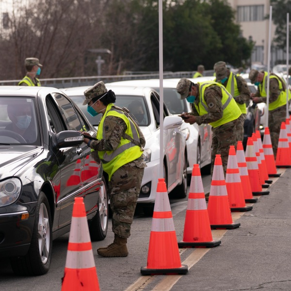 Members of the National Guard help motorists check in at a federally-run COVID-19 vaccination site set up on the campus of California State University of Los Angeles on Feb. 16, 2021. (AP Photo/Jae C. Hong)