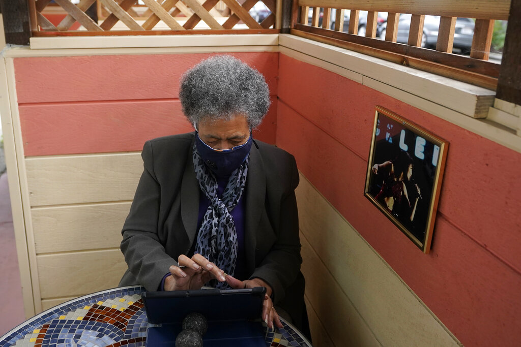 Lynnette White uses her tablet in San Francisco, Tuesday, Feb. 16, 2021. (AP Photo/Jeff Chiu)