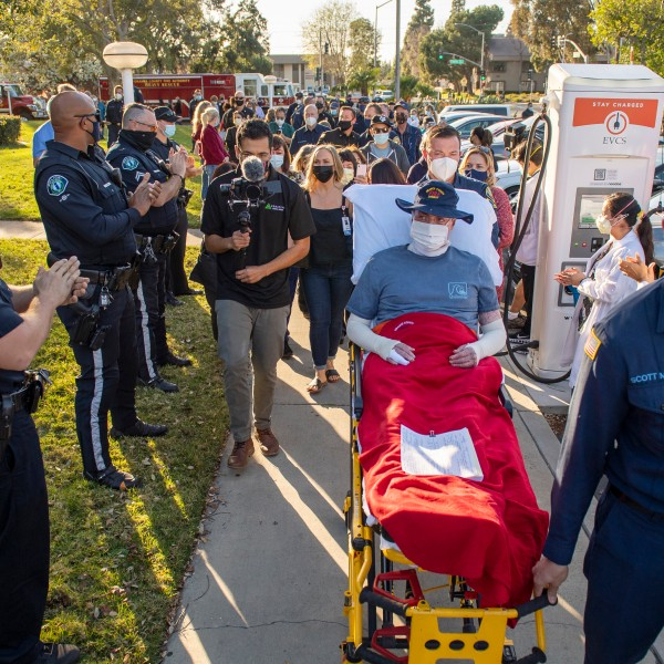 Dylan Van Iwaarden, an Orange County Fire Authority hand crew firefighter, is wheeled on a gurney as he leaves the Orange County Global Medical Center as scores of firefighters, police and medical personal line the sidewalk to cheer him on in Santa Ana on Feb. 17, 2021. (Leonard Ortiz / The Orange County Register via Associated Press)
