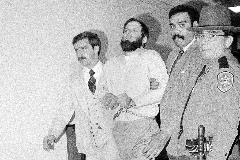 In this Nov. 23, 1981, file photo, Rockland County and others lead a handcuffed David Gilbert from Rockland County Court in New City, N.Y., after a hearing in Gilbert's felony murder case. Gilbert was convicted of murder in the deaths of two Nyack police officers and a Brink's guard during an infamous botched robbery considered one of the last gasps of 60's radicalism. Gilbert's son Chesa Boudin, now the San Francisco chief District Attorney, and others are seeking clemency from New York Gov. Andrew Cuomo for Gilbert, now 76 and still imprisoned for the Oct. 20, 1981, robbery. The case is more pressing due to the increased risk of COVID-19 among prisoners. (AP Photo/David Handschuh, File)