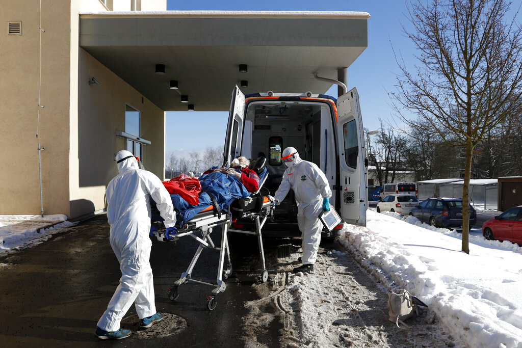 In this Friday, Feb. 12, 2021, file photo, medical workers move a COVID-19 patient into an ambulance at a hospital overrun by the COVID pandemic in Cheb, Czech Republic. (AP Photo/Petr David Josek/File)