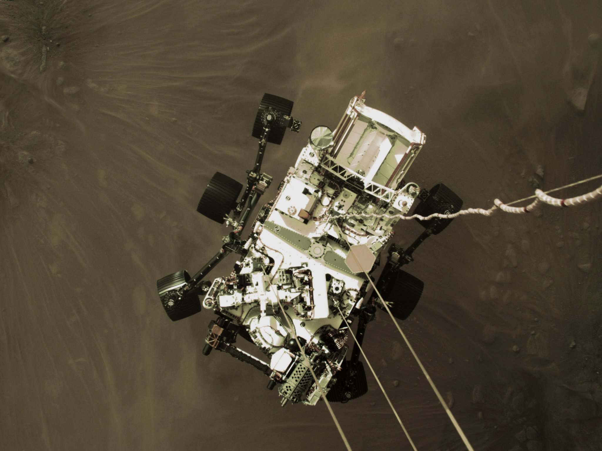 This Feb. 18, 2021 photo provided by NASA shows the Perseverance rover lowered towards the surface of Mars during its powered descent.