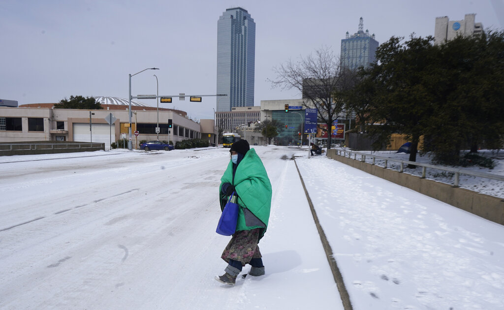 In this Feb. 16, 2021, file photo, a woman wrapped in a blanket crosses the street near downtown Dallas. (AP Photo/LM Otero, File)