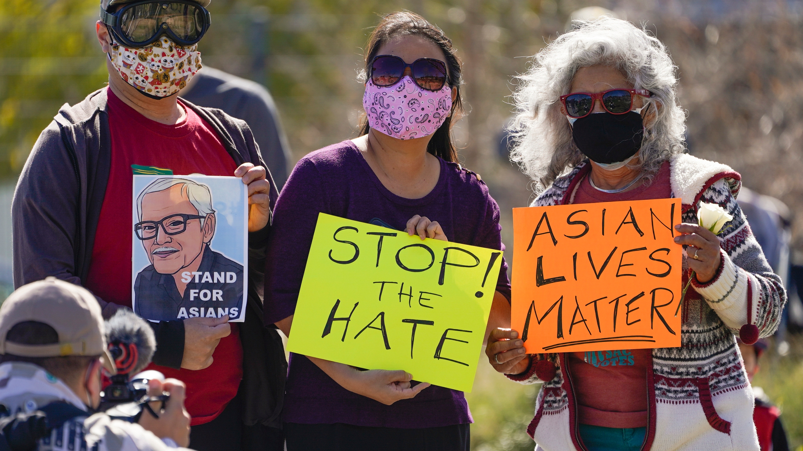 A man holds a portrait of late Vichar Ratanapakdee, left, a 84-year-old immigrant from Thailand, who was violently shoved to the ground in a deadly attack in San Francisco, during a community rally to raise awareness of anti-Asian violence and racist attitudes, in response to the string of violent racist attacks against Asians during the pandemic, held at Los Angeles Historic Park near the Chinatown district in Los Angeles on Feb. 20, 2021. (Damian Dovarganes / Associated Press)