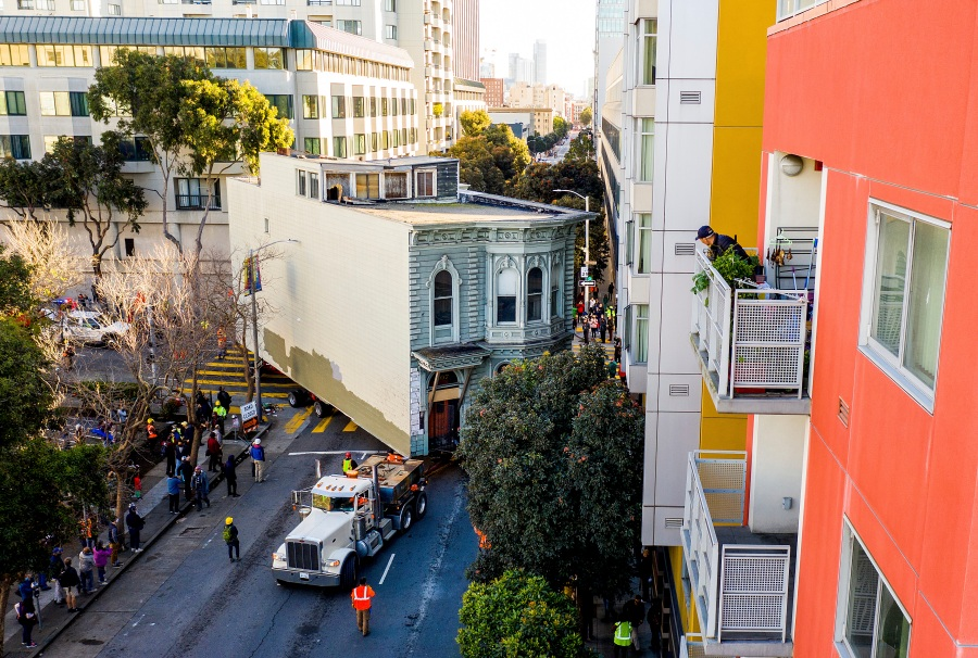 A man watches from a balcony as a truck pulls a Victorian home through San Francisco on Sunday, Feb. 21, 2021. (AP Photo/Noah Berger)