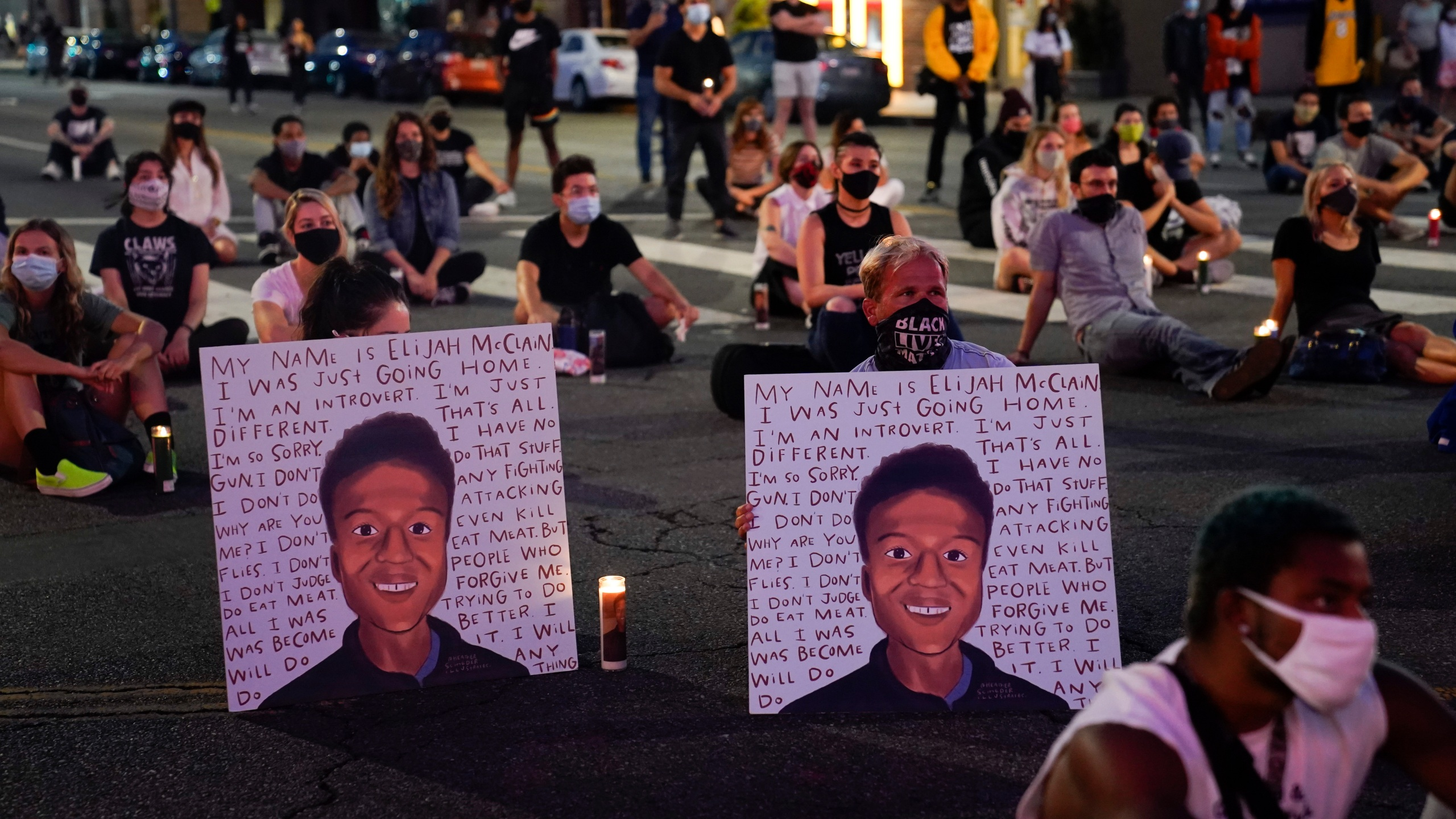 In this Aug. 24, 2020, file photo, two people hold posters showing images depicting Elijah McClain during a candlelight vigil for McClain outside the Laugh Factory in Los Angeles. (Jae C. Hong/Associated Press)