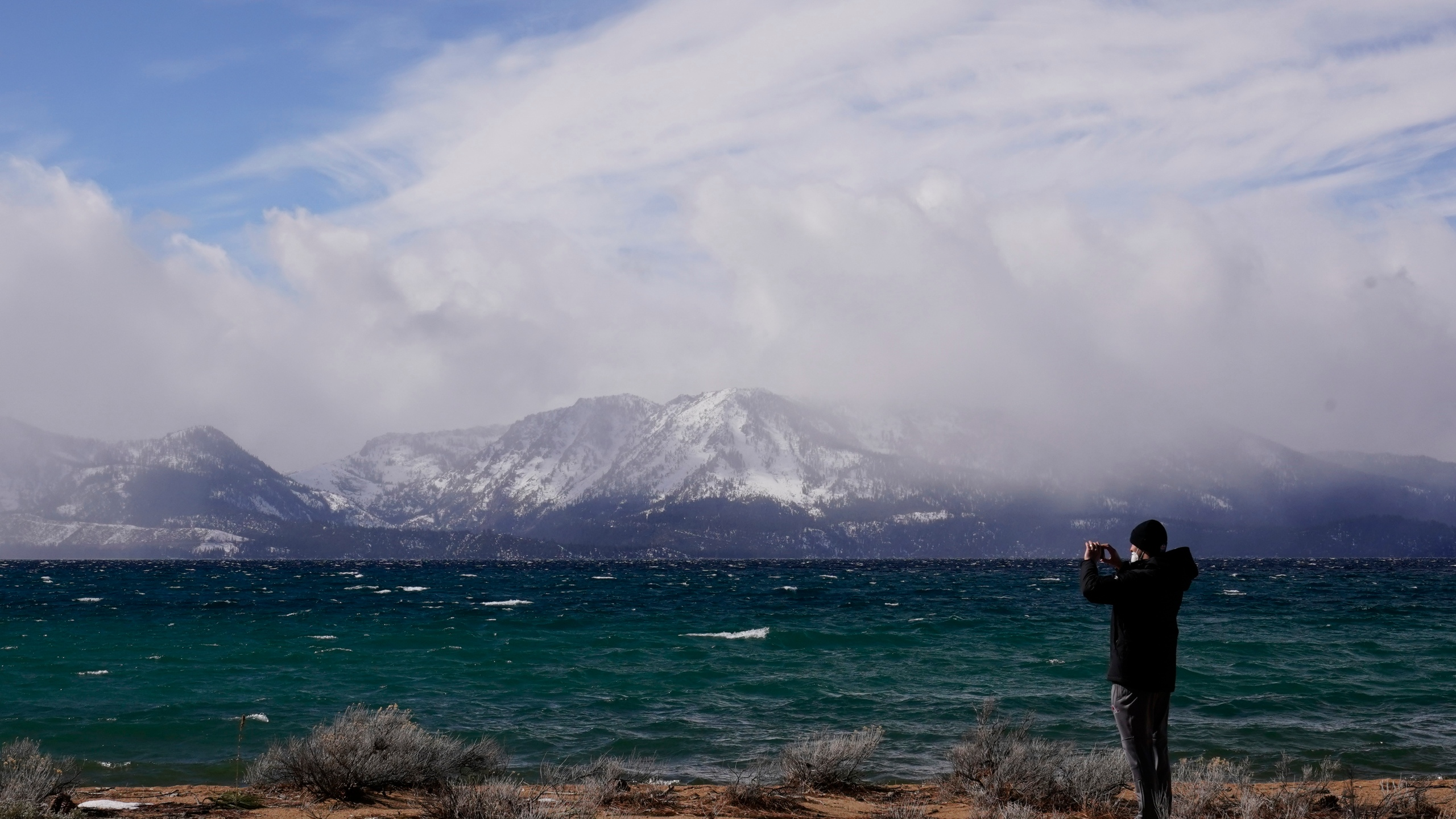 "In this Friday, Feb. 19, 2021 file photo, a person takes in the view of Lake Tahoe along the shore of the Edgewood Tahoe Resort, in Stateline, Nev. Researchers at Lake Tahoe are gaining confidence in a new weapon in their arsenal to combat the spread of invasive weeds that rob the alpine lake of its clarity, tiny bubbles. Conservationists are partnering with local property owners to expand the use of the so-called ""bubble curtains"" to halt the spread of non-native plants in the waters straddling the California-Nevada line, the Tahoe Daily Tribune reports. (AP Photo/Rich Pedroncelli, File)"