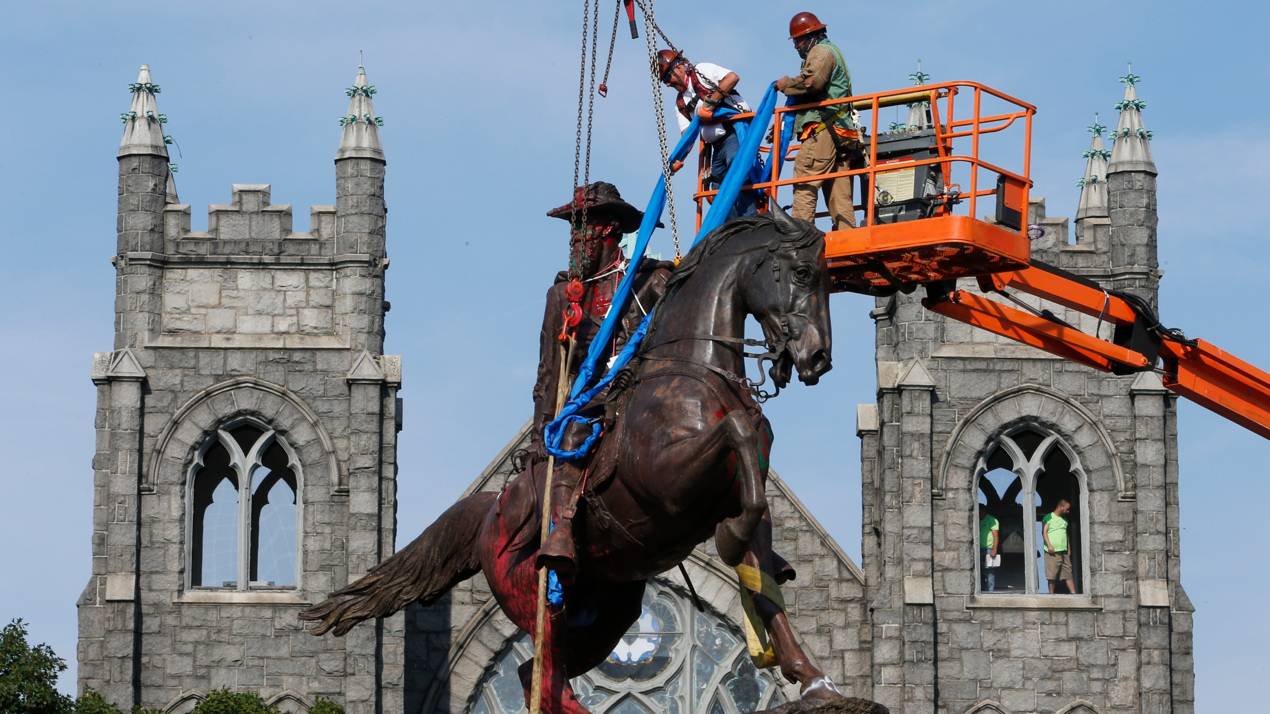 In this July 7, 2020, file photo, crews attach straps to the statue Confederate General J.E.B. Stuart on Monument Avenue in Richmond, Va. At least 160 Confederate symbols were taken down or moved from public spaces in 2020. That's according to a new count the Southern Poverty Law Center shared with The Associated Press. (AP Photo/Steve Helber, File)