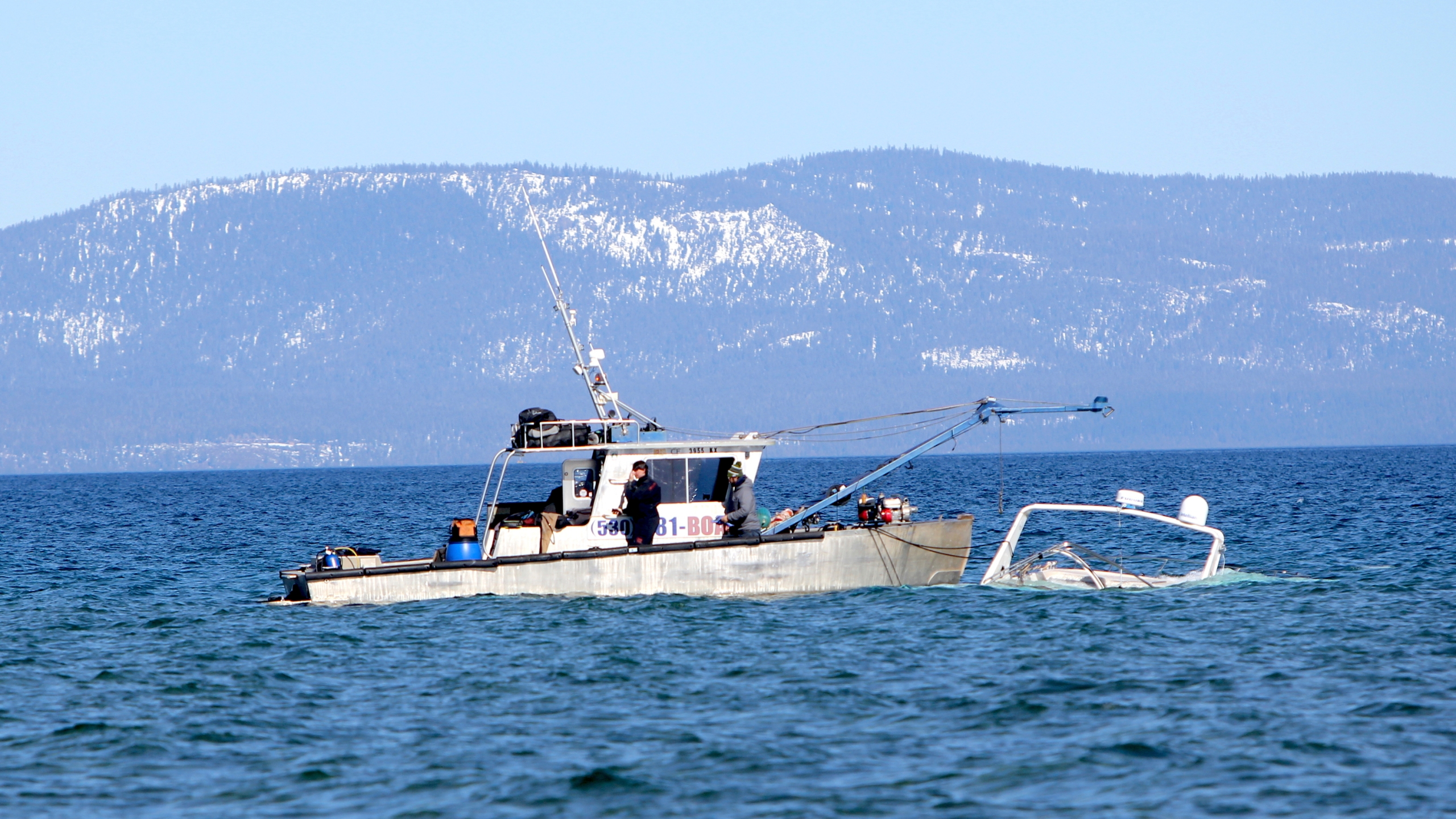 A crew for High Sierra Marine Inc. recovers a sunk boat , Tuesday, Feb. 23, 2021, of the shore of South Lake Tahoe. (Bill Rozak/The Tahoe Tribune via AP)