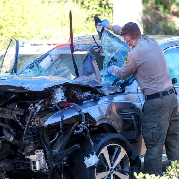 A law enforcement officer looks over a damaged vehicle following a rollover accident involving golfer Tiger Woods, Tuesday, Feb. 23, 2021, in the Rancho Palos Verdes suburb of Los Angeles.(AP Photo/Ringo H.W. Chiu)