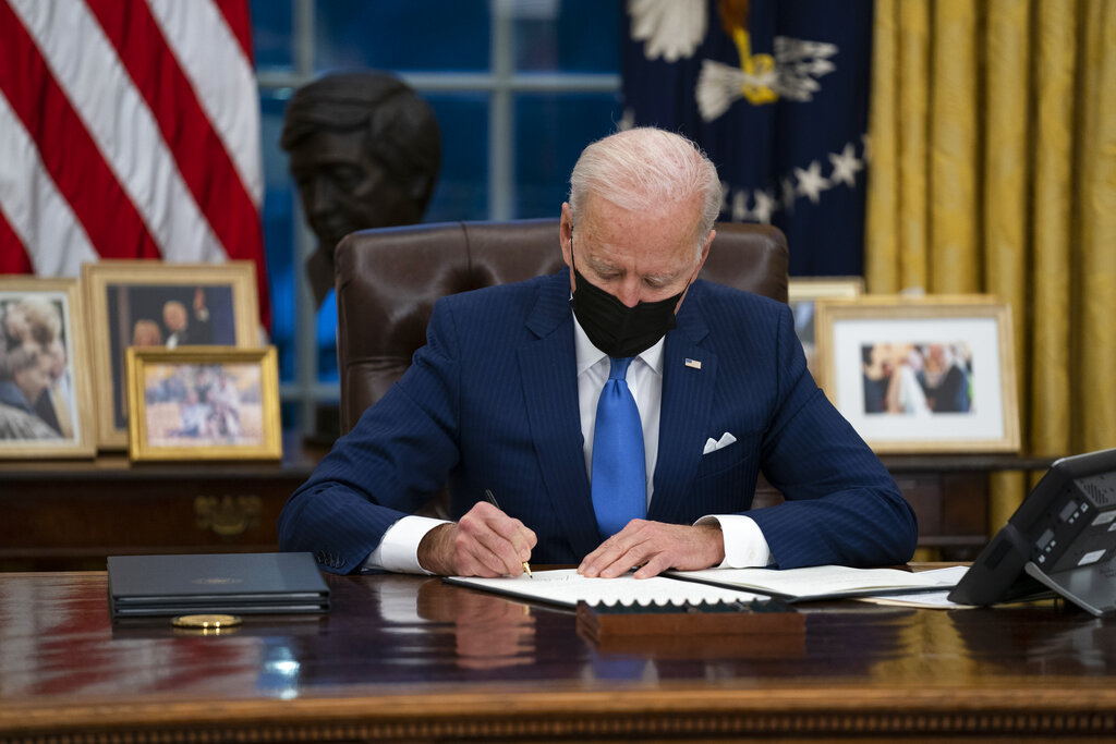 In this Feb. 2, 2021, file photo, President Joe Biden signs an executive order, in the Oval Office of the White House, in Washington. (AP Photo/Evan Vucci, File)
