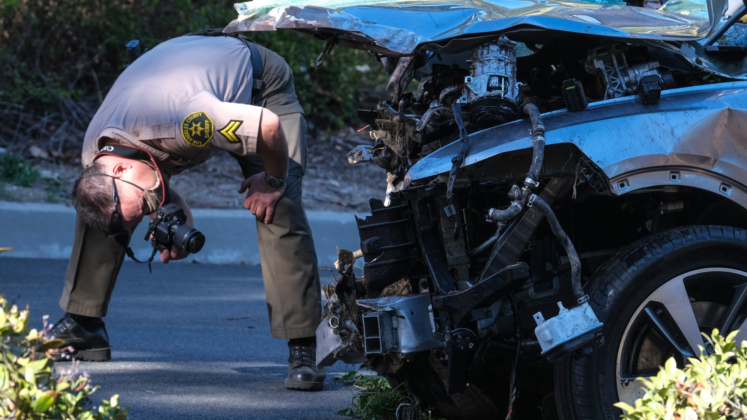 A law enforcement officer looks over a damaged vehicle following a rollover accident involving golfer Tiger Woods on Feb. 23, 2021, in the Rancho Palos Verdes suburb of Los Angeles. (Ringo H.W. Chiu / Associated Press)
