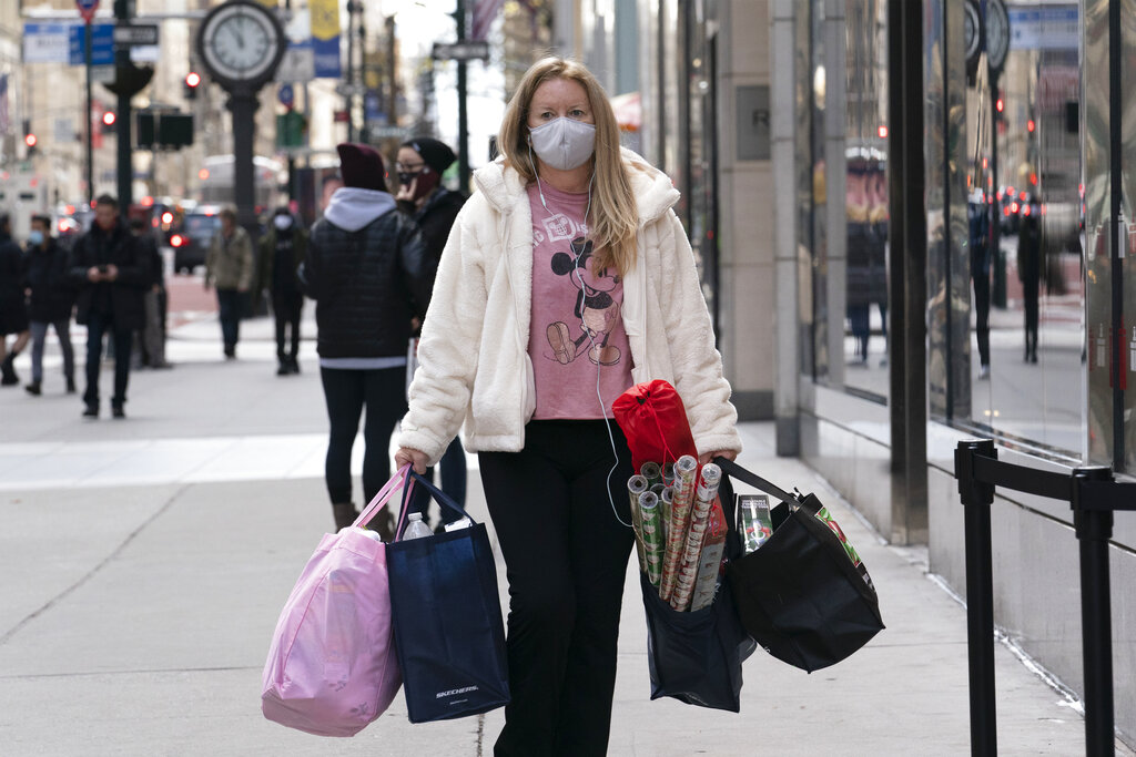 In this Dec. 10, 2020 file photo, a woman carries shopping bags in New York. (AP Photo/Mark Lennihan, File)