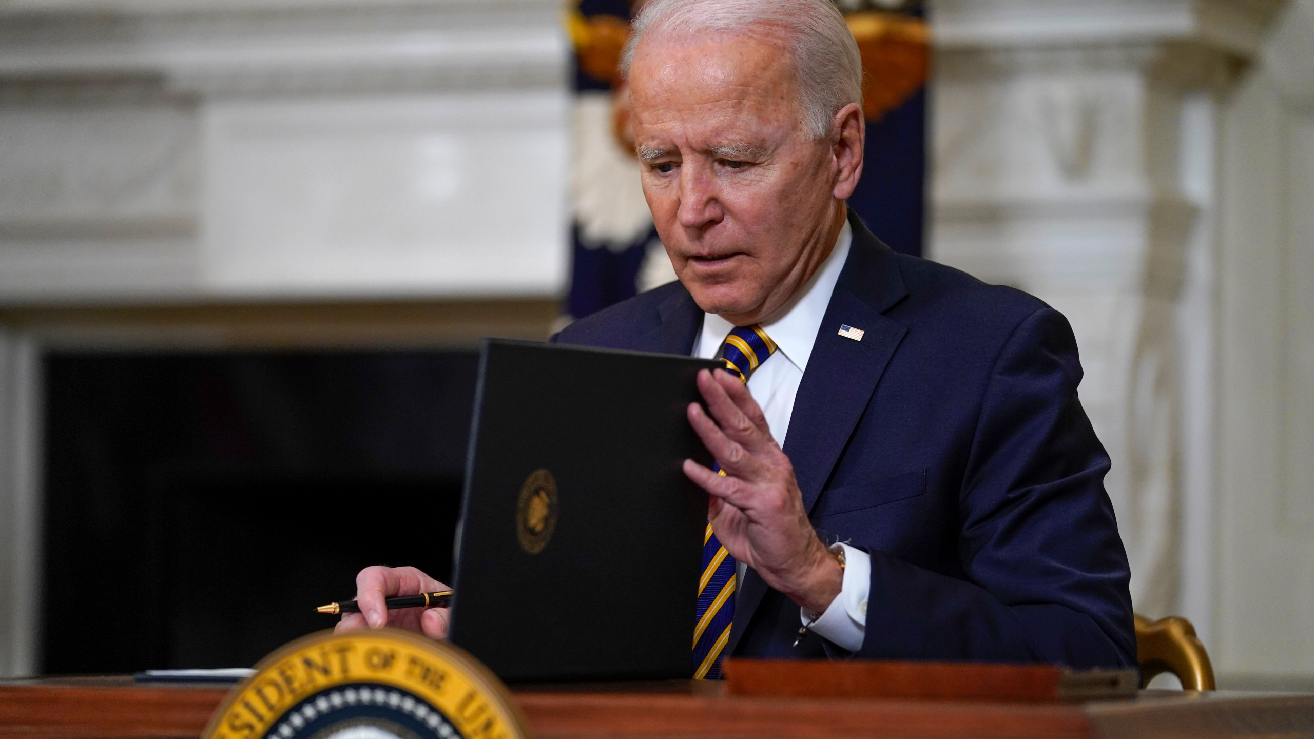 President Joe Biden closes the folder after signing an executive order relating to U.S. supply chains, in the State Dining Room of the White House on Feb. 24, 2021. (Evan Vucci / Associated Press)