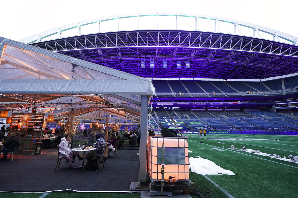 People eat dinner in an outdoor dining tent set up at Lumen Field, the home of the Seattle Seahawks NFL football team, Thursday, Feb. 18, 2021, in Seattle. (AP Photo/Ted S. Warren)