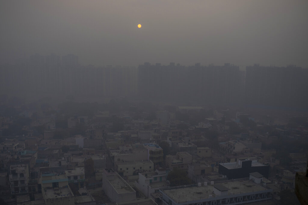 In this Saturday, Jan. 2, 2021 file photo, the morning sun is seen through a blanket of smog on the outskirts of New Delhi, India. (AP Photo/Altaf Qadri)