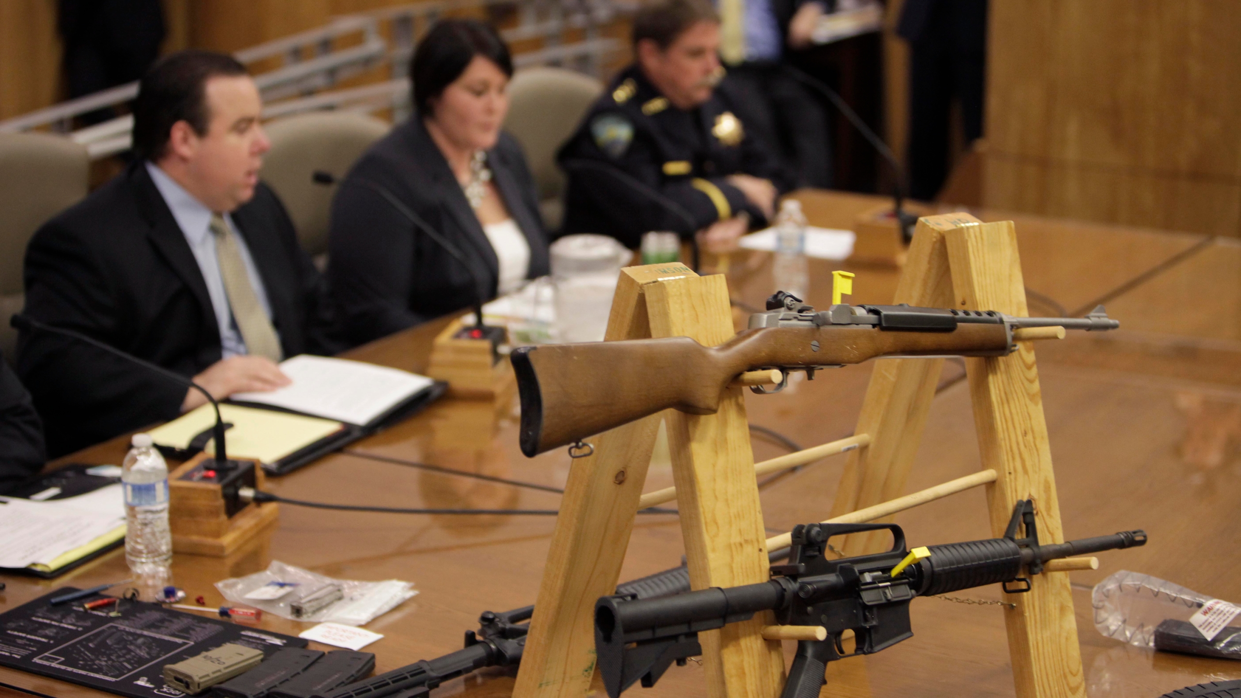 Semi-automatic rifles and large capacity magazines are displayed during a joint legislative informational hearing about gun control at the Capitol in Sacramento on Jan. 29, 2013. (Steve Yeater / Associated Press)