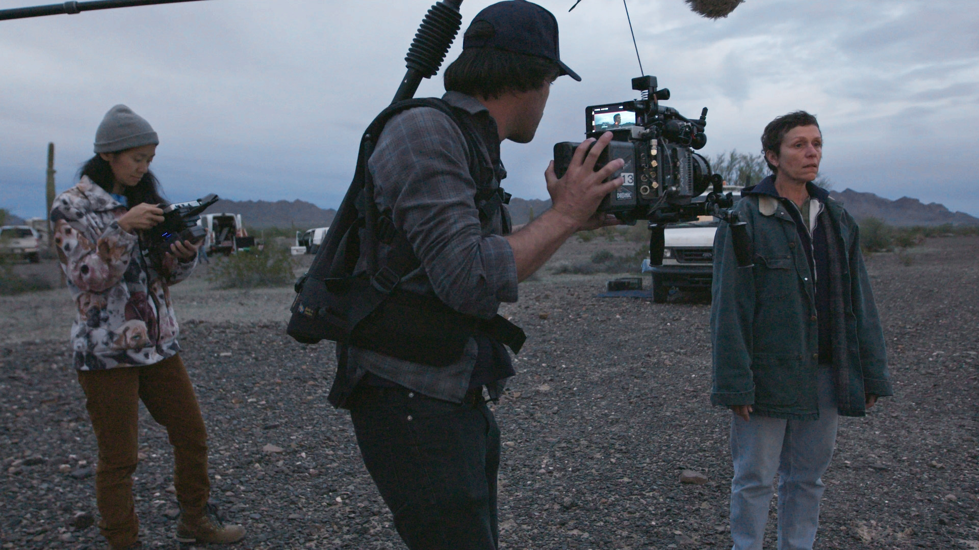 "This image released by Searchlight Pictures shows writer-director Chloé Zhao, from left, director of photography Joshua James Richards and actress Frances McDormand on the set of ""Nomadland."" Zhao has made cinema of rugged authenticity, relying frequently on non-professional actors and moments of serendipity while filming. She is nominated for a Golden Globe for best director. (Searchlight Pictures via AP)"