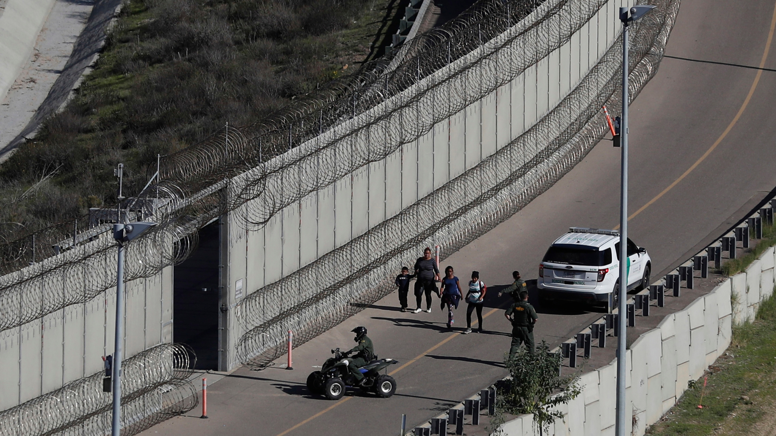 In this Dec. 16, 2018, file photo, Honduran asylum seekers are taken into custody by U.S. Border Patrol agents after the group crossed the U.S. border wall into San Diego, in California, seen from Tijuana, Mexico. The state of California is freeing up to $28 million to help asylum-seekers released in the U.S. with notices to appear in court with hotels, medical screenings, and transportation. California's generosity is a stark contrast to Arizona and Texas, where border state officials have challenged and sharply criticized President Joe Biden's immigration policies. (AP Photo/Moises Castillo, File)