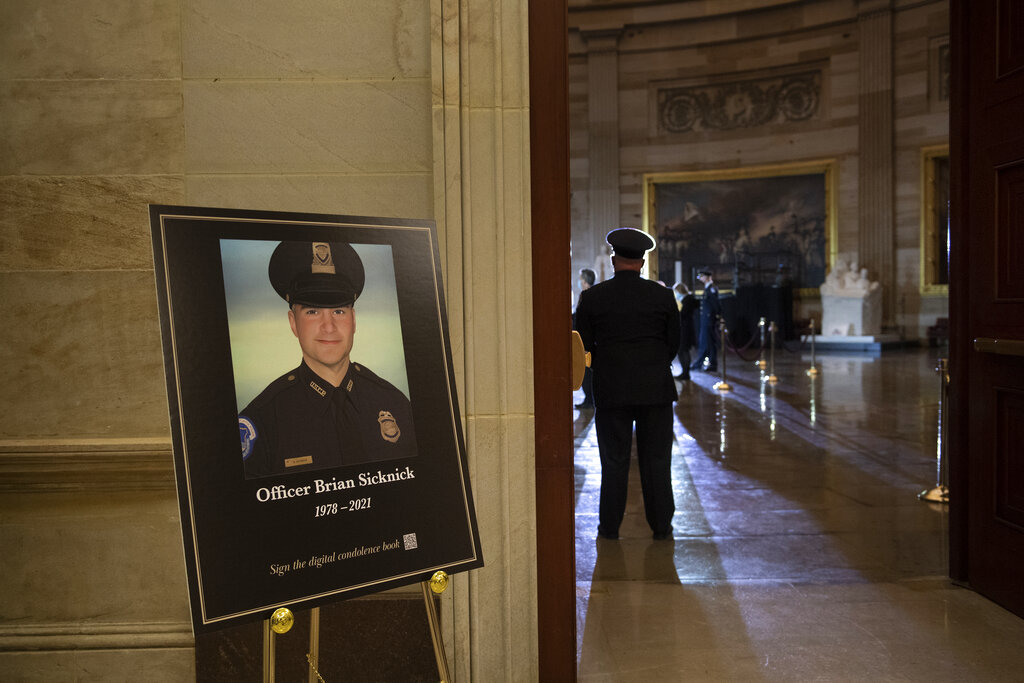 In this Feb. 2, 2021, file photo a placard is displayed with an image of the late U.S. Capitol Police officer Brian Sicknick on it as people wait for an urn with his cremated remains to be carried into the U.S. Capitol to lie in honor in the Capitol Rotunda in Washington. (Brendan Smialowski/Pool via AP, File)